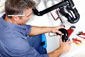 stock photo of adjustable-spanner  - Young smiling plumber fixing a sink in the kitchen - JPG