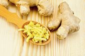 picture of root vegetables  - Wooden spoon with grated ginger ginger root against a wooden board - JPG
