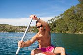 foto of canoe boat man  - Handsome young man on a canoe on a lake - JPG