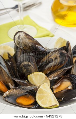 Plate Of Coocked Mussels With Lemon Isolated Over White