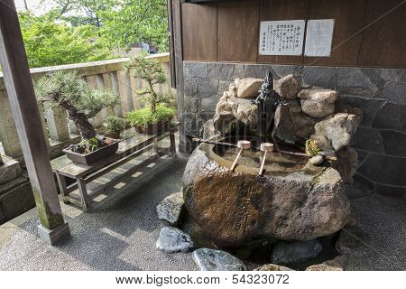 Purification Ladles And Bonsai Trees In The Kanazawa Old Town, Japan.
