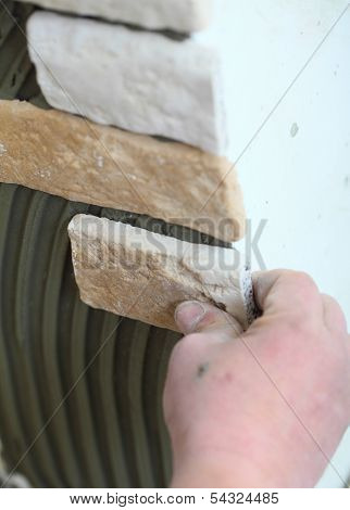 Construction Worker Installing Tiles On A Wall