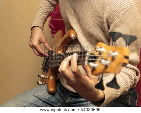 Guitarist Sitting And Playing A Bass Guitar