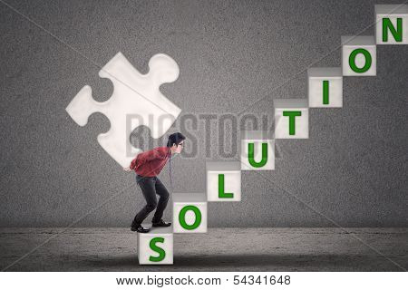 Businessman Bring Puzzle Solution On Grey