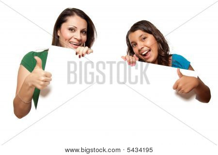 Pretty Hispanic Girl And Mother Holding Blank Board
