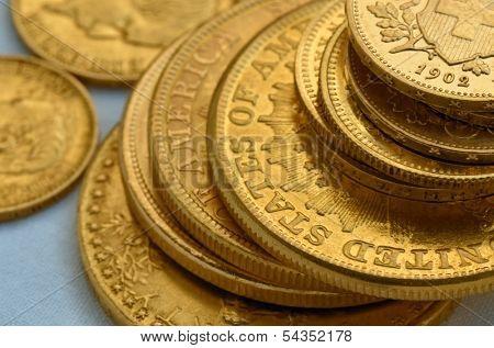 Few old golden coins, swiss francs, American liberty twenty dollars, russian rubles. Still life.