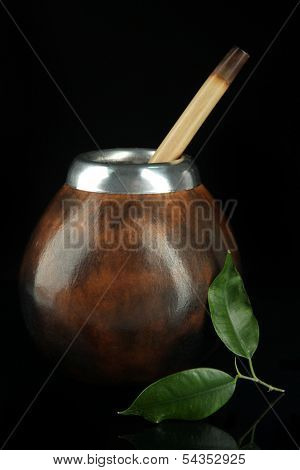 Calabash and bombilla with yerba mate isolated on black