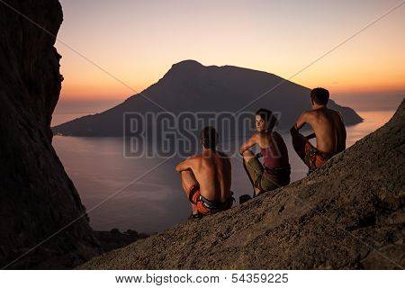 Rock climbers wearing safety harness at sunset