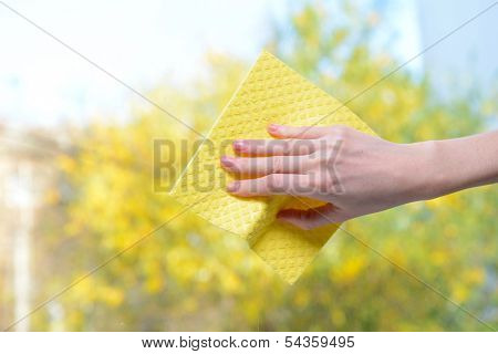 Hands with  napkin cleaning  window