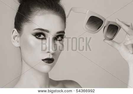 Duotone portrait of young beautiful stylish girl with vintage sunglasses in her hand