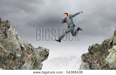 Young businessman jumping over mountain gap. Risking in business