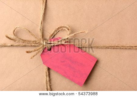 Closeup of a gift tag on a Christmas present. The package is wrapped in plain brown paper and twine. The red tag is blank. Horizontal format.