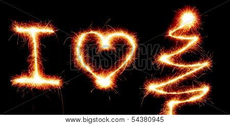 I Love Christmas, heart shape and a Christmas tree made with a sparkler light on black background