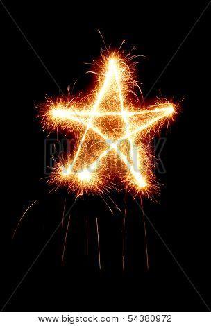 Star made by sparkler isolated on black background. Christmas, holiday, celebration symbol.
