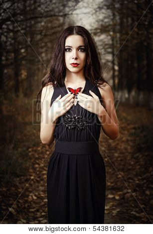 Beautiful Girl Holds Red Butterfly In Hands. Outdoor Portrait