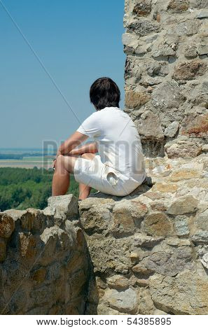 Young Man Sitting On The Wall Of Medieval Fortress