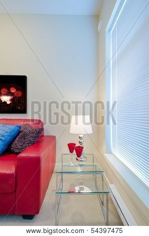 Interior design with sofa, pillows, lamp and two glasses on end table