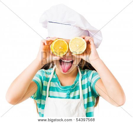 little girl in chef hat with two halves of a lemon in the eyes shows tongue on a white background