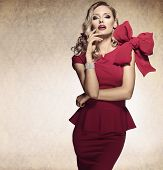 stock photo of aristocrat  - sophisticated elegant lady in red dress with a big bow and jewellery looking in camera with arrogant expression - JPG