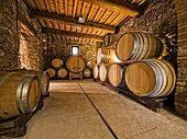 stock photo of keg  - oak wine barrels stacked in a winery cellar - JPG