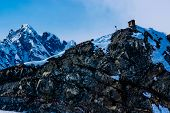 stock photo of outhouses  - A Mountain Outhouse Pearched Precariously on a Snow Covered Steep Ledge of an Icy Mountain Peak in Alaska - JPG