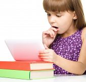 Surprised young girl is using tablet while studying geography, isolated over white
