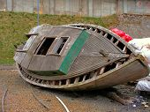 picture of raunchy  - an old derelict wooden boat lying in a harbour area - JPG