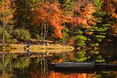 pic of dock a pond  - A highly reflective lake with fall colored trees - JPG