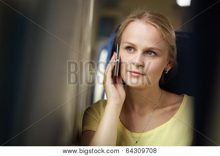 Young woman listening to her mobile while travelling by train