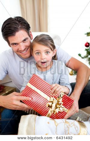 Portrait Of A Surprised Little Girl Holding A Christmas Present