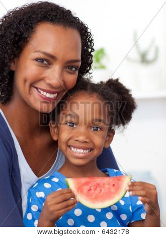 Smiling Mother And Her Daughter Eating Fruit