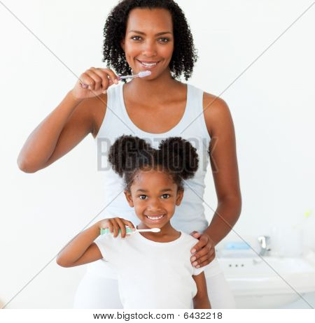 Mother And Her Daughter Brushing Their Teeth