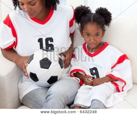 Mother And Her Daughter Watching A Football Match