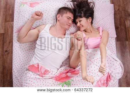 Young Couple Waking Up In Bed And Sipped