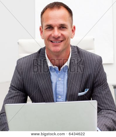 Portrait Of A Smiling Businessman Using A Laptop