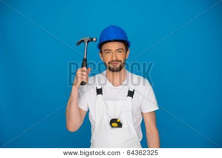 Smiling workman or builder wearing a hardhat and dungarees holding up a claw hammer in his hand on a blue background with copyspace