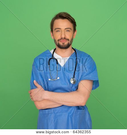 Confident friendly young male doctor or nurse standing with a stethoscope around his neck with crossed arms smiling at the camera on a green background