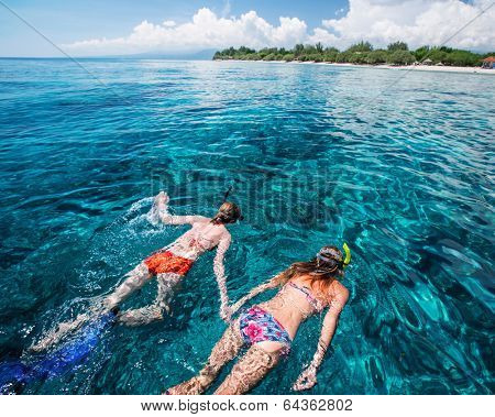 Two ladies snorkeling in the clear tropical sea near the island of Gili Trawangan, Indonesia