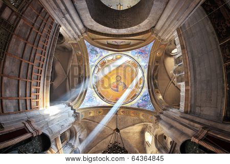 JERUSALEM, ISRAEL - MARCH 9, 2012: Facilities in the Holy Sepulchre. The magnificent round arch of a ceiling is shined with sun