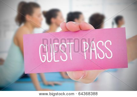 Woman holding pink card saying guest pass against yoga class in gym