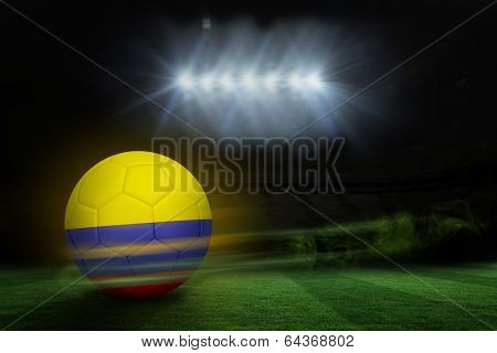 Football in colombia colours against football pitch under spotlights