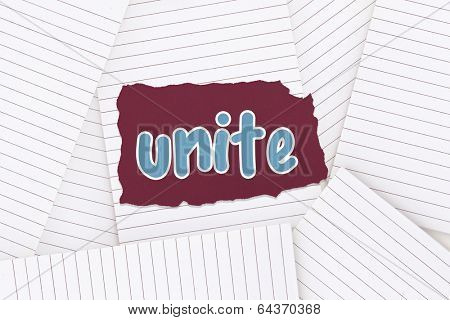 The word unite against lined paper strewn over surface