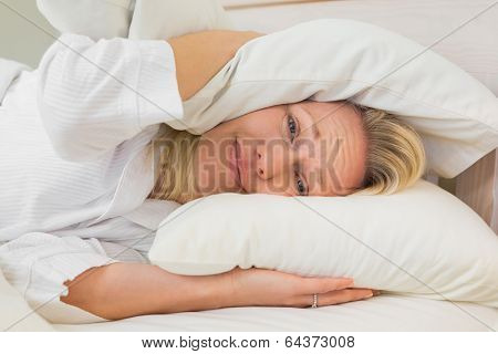 Portrait of irritated woman covering ears with pillows while lying in bed at home