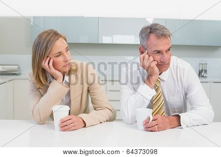 Unhappy business couple not talking after an argument in the kitchen at home