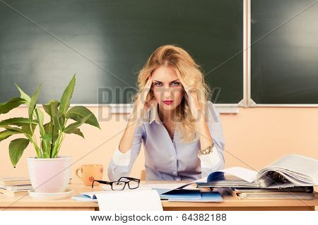 Tired teacher checking the tests.