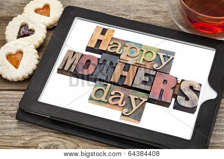 Happy Mother Day in vintage letterpress wood type on a digital tablet with a cup of tea and heart cookies