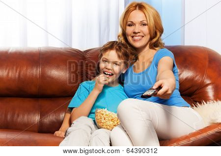 Happy mother and child sitting watching TV