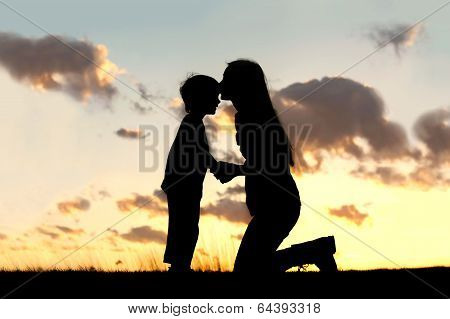 Mother Lovingly Kissing Little Child At Sunset