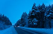 stock photo of nightfall  - Car traveling on road in winter forest - JPG