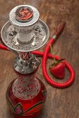 foto of shisha  - An ornate Syrian sheesha or hooka water pipe on wood table - JPG